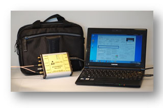 pocketBERT pictured next to a computer and brief case; the affordable, portable 10 Gb/s PRBS pattern generator, checking unit makes it easy.